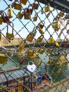 Love locks on bank parapet leading to Pont des Arts