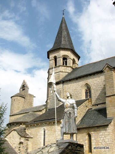 Villeneuve d'Aveyron Church with the statue of Joan of Arc